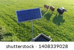 Small photo of Low altitude aerial photo of single solar panel powering water pump cattle in background looking at camera photovoltaic cells absorb sunlight as a source of energy to generate electricity