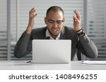 Small photo of Angry stressed african business man using laptop mad about broken computer online problem annoyed with slow stuck laptop error, crazy about system virus or data loss, outraged with website mistake