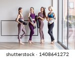 Small photo of Cheerful women wearing activewear standing near large window hold yoga mats ready start fitness training and rejoice at meeting. The concept of sports lifestyle and like-minded people. Yoga concept