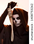 Small photo of woman in death costume holding hanging noose isolated on white