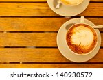 Latte art concept. Two cups with cappuccino (hot coffee with milk foam) and canella (cinnamon) on wooden table at street cafe (coffe bar). Vintage style. Copy-space. Outdoor shot. - stock photo
