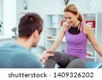 Small photo of Feeling ticklish. Nice pleasant woman looking at her knee while feeling ticklish during medical checkup