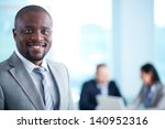 Small photo of Image of African-American business leader looking at camera in working environment