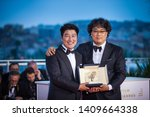 """Small photo of CANNES, FRANCE - MAY 25, 2019: Director Bong Joon-Ho with Kang-Ho Song, winner of the Palme d'Or award for his film """"Parasite"""" poses at thephotocall for Palme D'Or Winner - 72 Cannes Film Festival"""