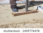 Small photo of Man tamp the sand with a homemade tool