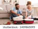 afro couple packing clothes... | Shutterstock . vector #1409865095