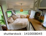 Inside the camper van. Unmade bed, pillows, white wooden interior decoration with lamp center. A cozy sleeping place for a young couple to sleep inside a camper for traveling. - stock photo