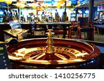 Roulette table in casino with many games and slots in the background. Casino interior, golden equipment and luxury feel. Selective focus. Roulette wheel is golden and shiny. - stock photo