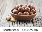 macadamia nuts on wooden... | Shutterstock . vector #1410293402