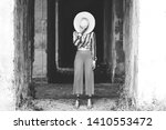 Small photo of Stylish woman hides her face behind a straw hat. Trend creative brash concept. Monochrome image. Glossy vogue background