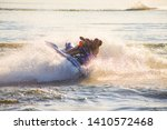 young man and woman drive on the jetski above the water at sunset .silhouette. spray.