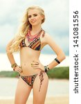 Portrait of beautiful long hair blonde model with great tan smiling, posing and standing at seaside. Bikini fashion. Trendy luxurious accessories (necklace, bracelets). Cloudy weather. Outdoor shot - stock photo