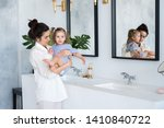 a young woman and a baby wash... | Shutterstock . vector #1410840722