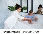 a young woman and a baby wash... | Shutterstock . vector #1410840725