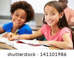 pupils studying at desks in... | Shutterstock . vector #141101986