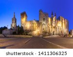 Palace of the Popes, once a fortress and palace, one of the largest and most important medieval Gothic buildings in Europe and Avignon Cathedral during evening blue hour, Avignon, southern France