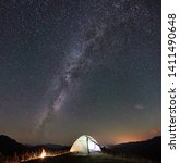 Panoramic view of tourist camping at night in the mountains. Glowing tent and bonfire under incredibly beautiful night sky full of stars and Milky way. Tourism adventure astrophotography concept