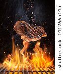 Small photo of Tasty beef steaks flying above cast iron grate with fire flames. Freeze motion barbecue concept.