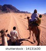 Girl on trip with camels through Wadi Rum desert in Jordan - stock photo