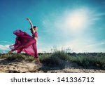 Woman in airy red dress running on sand beach - stock photo
