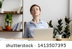 Small photo of Businesswoman breathing, stretching shoulders after hard work feeling discomfort at office desk work. Young tired woman take minute pause keeping eyes closed. Uncomfortable chair, overwork on laptop