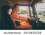 Garbage removal worker in protective clothing driving a dump truck - stock photo