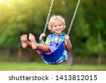 Small photo of Child playing on outdoor playground in rain. Kids play on school or kindergarten yard. Active kid on colorful swing. Healthy summer activity for children in rainy weather. Little boy swinging.