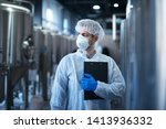 Technologist in protective white suit with hairnet and mask standing in food factory. - stock photo