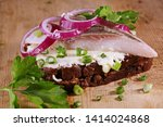 Stock photo sandwich with herring red onion rye bread on a brown table tradition danish open sandwich 1414024868
