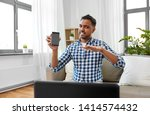 Small photo of blogging, videoblog and people concept - displeased indian male blogger with camera recording video review of smartphone at home and making so-so gesture