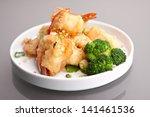 Thai style honey shrimp dish presented beautifully on a round white plate. - stock photo