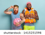 Small photo of Mixed race two men stare at camera, shocked witness emergency situation on water. Surprised redhead bearded man wears goggles and striped t shirt, holds beach ball, Afro man in lifejacket and swimhat