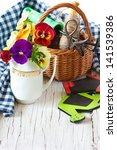 Beautiful garden pansy flowers, garden tools and old basket on an old wooden board. - stock photo