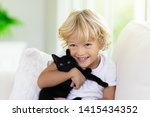 Stock photo child playing with baby cat kid holding black kitten little boy snuggling cute pet animal sitting 1415434352