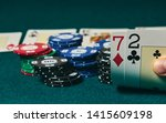 Bad poker gamble or unlucky hand concept with player going all in with 2 and 7 (two and seven) offsuit also called unsuited, considered the worst hand in poker preflop (before the flop is revealed)