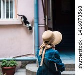 Small photo of Blue jacket, big hat, and a jumpy cat.
