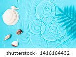 Small photo of Blue water texture background on the noon sunlight with seashells and tropical leaves shadow.