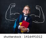 Small photo of Cute child boy in school uniform and glasses. Go to school for the first time. Child with school bag and books. Kid in class room near chalkboard with muscles on it. Back to school