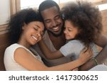 Small photo of Happy affectionate african american family of three bonding embracing, cute kid child daughter and loving parents cuddling congratulating dad with fathers day hugging smiling daddy laughing together