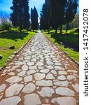 landscape with stone path of ancient Roamn road Via Appia Antica in vanishing point in big park area in Rome, Italy
