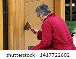 a man paints a garage with a... | Shutterstock . vector #1417722602