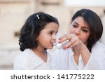 mother giving water to little... | Shutterstock . vector #141775222