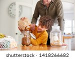 father helping son to refill... | Shutterstock . vector #1418266682