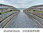 A rustic wooden boardwalk is a common sight in Florida beaches such as at the Indian Rocks beach where beachgoers are led to the serene and beautiful waters of Gulf of mexico