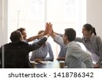 Excited multi racial businesspeople sitting at table conference room achieve corporate success celebrating market leadership giving high five hold hands together feels happy. Team spirit unity concept - stock photo