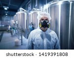 Small photo of Portrait of industrial worker technologist wearing hazmat suit in production plant. Man in white protective uniform with hairnet and protective mask handling hazardous chemicals.