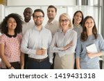 Small photo of Smiling multiethnic employees standing looking at camera making team picture in office together, happy diverse work group or department laugh posing for photo at workplace, show unity and cooperation