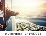 Feet On Boat Sailing At Sunris...