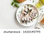 Stock photo salted herring fillet with spice herbs and onion on plate on white stone background with copy 1420190795
