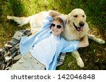 Stock photo portrait of cute lad embracing his fluffy friend while lying on grass 142046848